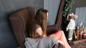 Attraktivt flickasammanträde på brun hemtrevlig stol i inre jul lager videofilmer