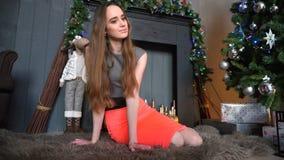 Attraktivt flickasammanträde på golvet i den mysiga inre lager videofilmer