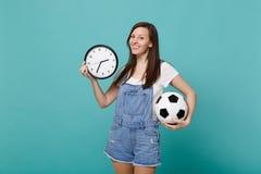 Attraktivt fotbollsfanjubel för ung kvinna upp, favorit- lag för service med fotbollbollen, rund klocka som isoleras på blått arkivbild