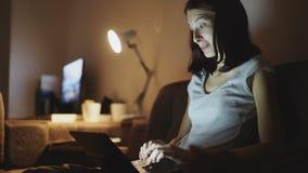 Attraktivt gladlynt kvinnasammanträde på soffan och ha en video appell med vänner på natten hemma arkivfilmer