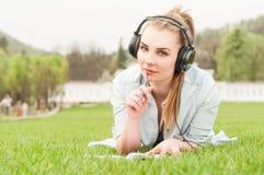 Attraktivt koppla av för flicka som är utomhus- medan lyssnande musik, och skriva Royaltyfri Fotografi