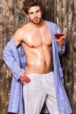 Attraktivt koppla av för grabb med alkoholdrinken Hud för sexig bröstkorg för man våt efter badhållvinglas macho ovårdat hår arkivfoton