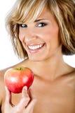 Attraktivt kvinnainnehav ett äpple arkivfoto