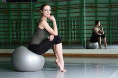 Attraktivt kvinnasammanträde med övningsbollen arkivbilder
