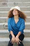 Attraktivt kvinnasammanträde på trappa utomhus och att le Arkivfoton