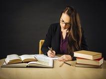 Attraktivt läraresammanträde på hennes skrivbordhandstil arkivfoton