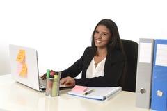 Attraktivt latinamerikanskt affärskvinnasammanträde på kontorsskrivbordet som arbetar på att le för datorbärbar dator som är lyck Royaltyfri Foto