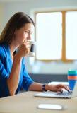 Attraktivt le sammanträde för affärskvinna på kontorsskrivbordet som rymmer en kopp kaffe Arkivfoton