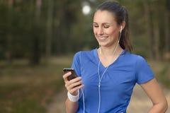 Attraktivt lyckligt kvinnaanseende som lyssnar till musik Royaltyfri Bild