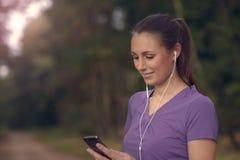 Attraktivt lyckligt kvinnaanseende som lyssnar till musik Arkivfoto