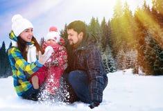 Attraktivt man, kvinna och barn på en bakgrund av ett jullandskap Royaltyfri Fotografi