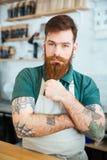 Attraktivt manligt baristaanseende och trycka på hans skägg Royaltyfri Foto
