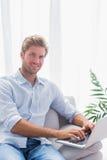 Attraktivt mansammanträde på soffan och använda hans bärbar dator Royaltyfri Bild