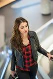 Attraktivt mode för ung kvinna som skjutas i galleria Härlig trendig ung flicka i svart läderomslag på rulltrappor i galleria Arkivfoto