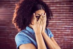 Attraktivt nederlag för ung kvinna bak händer arkivbild