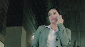 Attraktivt och le affärskvinnan som positivt talar på telefonen arkivfilmer