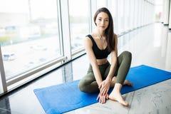 Attraktivt sammanträde för den unga kvinnan kopplar av i det mattt på golv efter yogautbildning i idrottshall royaltyfri bild
