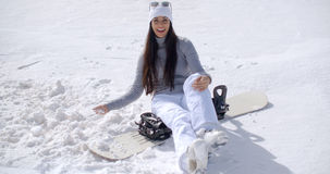 Attraktivt sammanträde för ung kvinna på hennes snowboard Fotografering för Bildbyråer