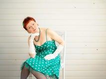 Attraktivt sammanträde för vuxen kvinna på stol Royaltyfri Foto