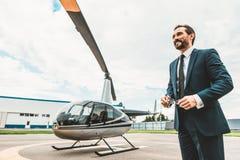 Attraktivt skäggigt affärsmananseende nära helikoptern och le arkivfoton