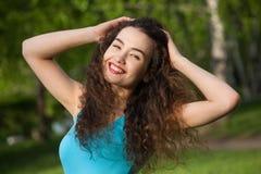 Attraktivt, ung flicka med lockigt långt hår som ler och gör selfie Fotografering för Bildbyråer