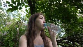 Attraktivt ung flickadricksvatten från den plast- flaskan i parkera Statisk video för kamera HD arkivfilmer