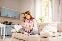 Attraktivt ung flickasammanträde på soffahandstilsms på mobiltelefonen Arkivbilder