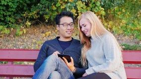 Attraktivt ung man- och kvinnasammanträde på en parkerabänk Tyck om den digitala tableten Koreansk man och Caucasian kvinna stock video