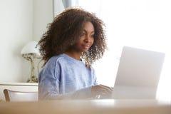 Attraktivt ungt afrikanskt kvinnasammanträde hemma och arbeta på bärbar datordatoren royaltyfri fotografi