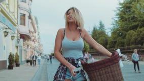 Attraktivt varmt, cykel för tappning för ung kvinna för passform som driftig slår hennes hår som ler seductively i centret lager videofilmer