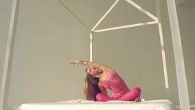 Attraktivt yogakvinnasammanträde i säng i lotusblommaposition stock video