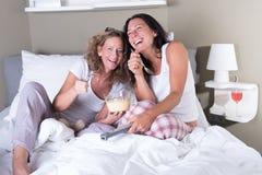 2 attratcive женщины сидя в кровати и смеяться над Стоковые Изображения