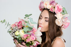 Attrative招标花玫瑰花圈嗅到的花束的妇女  免版税库存照片