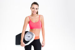Attrative happy sportswoman posing with weighing scale Stock Photos