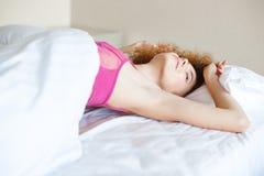 Attrative kusicielska kobieta w menchiach zasznurowywa stanika rozciąganie na łóżku Zdjęcia Royalty Free