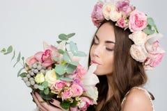 Attrative ofrece a la mujer en el ramo que huele de la guirnalda de las rosas de flores Foto de archivo libre de regalías