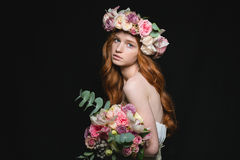 Attrative redhead woman posing with flowers. Portrait of attractive redhead woman posing with flowers over black background royalty free stock photography