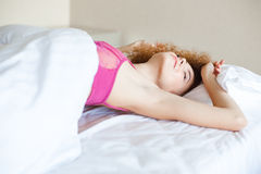 Attrative tempting woman in pink lace bra stretching on bed Royalty Free Stock Photos