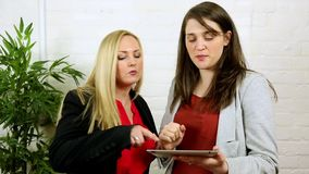 Attrative women using ipad tablet app and viewing pictures photos stock footage