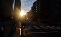 Attraversamento della strada nell'ambito della luce solare fotografia stock