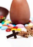 Attraversi contro le uova ed i dolci di cioccolato di pasqua Fotografia Stock