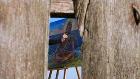 Attraverso una crepa in un recinto di legno, coperto di ragnatele, potete vedere la mano con la spazzola dell'artista, lei diping video d archivio