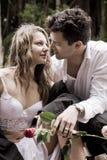 Attrayant heureux dans des couples d'amour se reposant au bord de la fontaine avec les roses rouges Photo stock