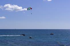 Attrazione dell'acqua - una barca rimorchia gli uomini su un paracadute sopra il mare Fotografia Stock