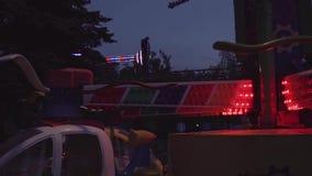 Attrazioni del parco di divertimenti con luce variopinta infiammante alla notte archivi video