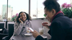 Attrcative mixed race woman sitting at the table in the street cafe talking cell phone while her friend surfing stock footage