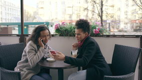 Attrcative mixed race woman sitting at the table in the street cafe talking cell phone while her friend surfing stock video footage
