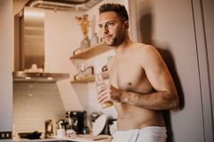 Attrctive young man with bare torso holding hand orange juice, looking out the window and smiling while standing in. Kitchen at home royalty free stock photography