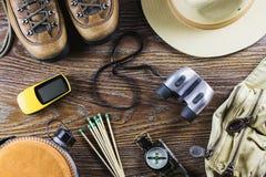Attrezzatura con gli stivali, bussola, binocolo, partite di viaggio o di escursione su fondo di legno Concetto attivo di stile di Fotografia Stock