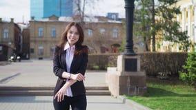 Attrezzatura d'uso dell'ufficio della bella giovane donna di affari felice che balla allegro sulla via davanti alla società stock footage